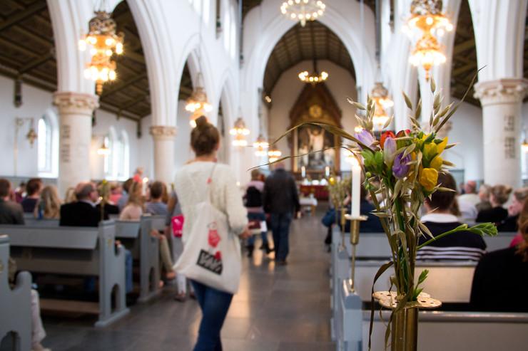 Kvinde på vej op ad kirkegulvet i en fyldt kirke