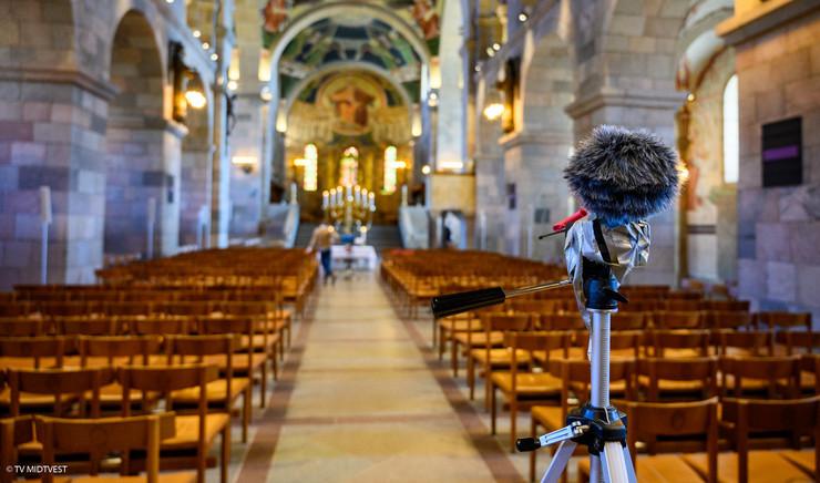 Kamera og mikrofon i forgrund af kirkerum