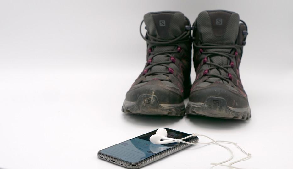 Støvler og iPhone med hovedtelefoner