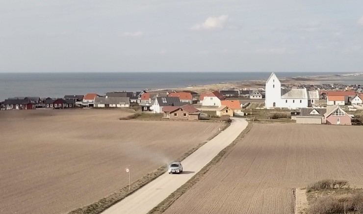 Luftbillede af bil på grusvej med kirke i baggrunden
