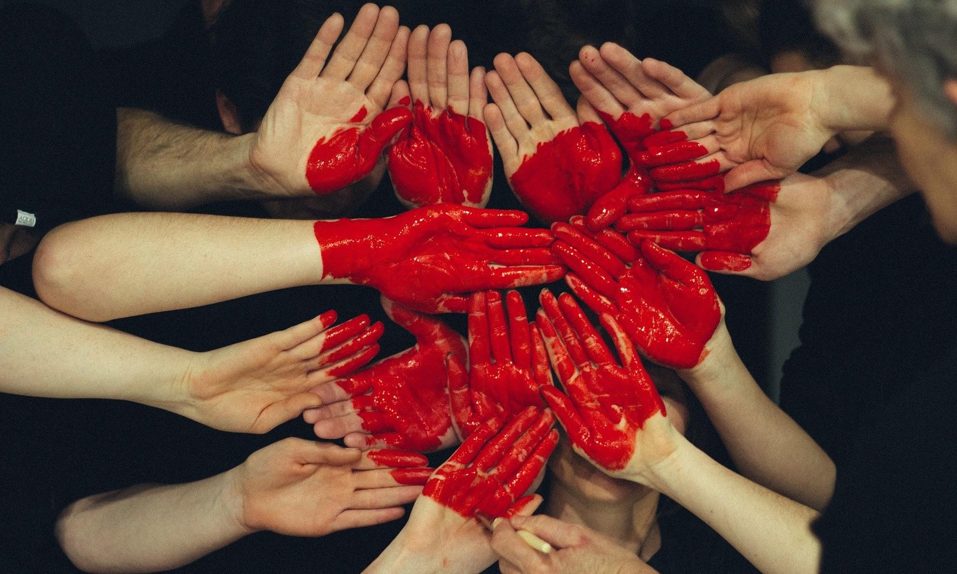 Rød maling på hænder danner hjerte