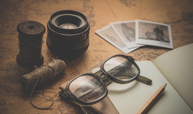 Fotos, objektiv og briller ved notesbog