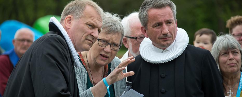Tre præster kigger fremad ud af billedet