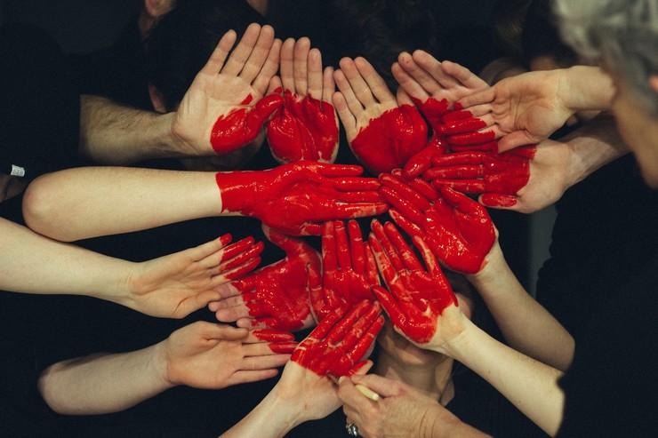 Hænder med rød maling der danner et hjerte