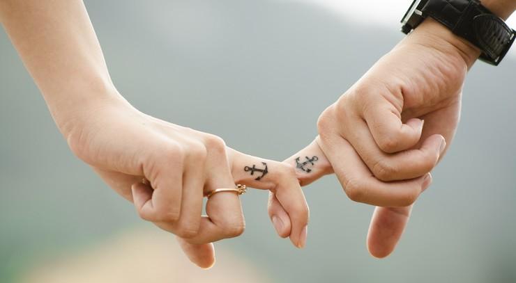 To holder i hånd